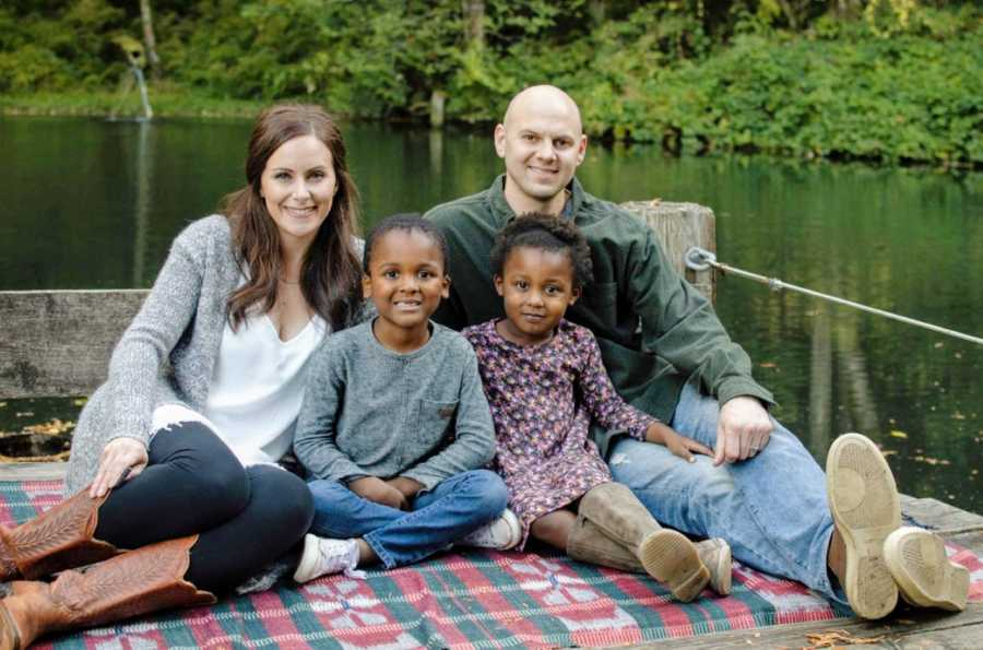Couple with their adopted children pose for a family photo next to a lake