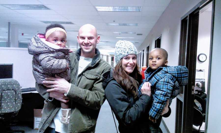 Adoptive parents hold their adopted siblings in winter gear