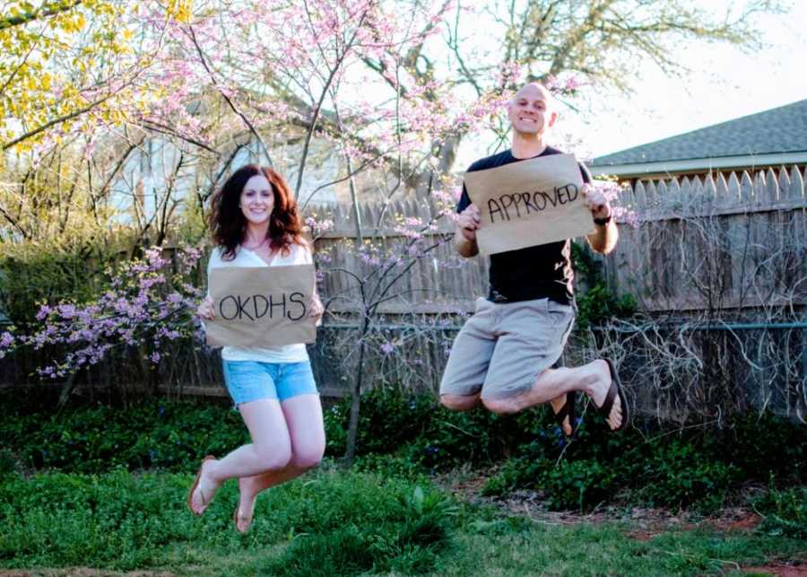 """Man and woman jump for joy in their backyard holding signs that say """"OKDHS APPROVED"""""""