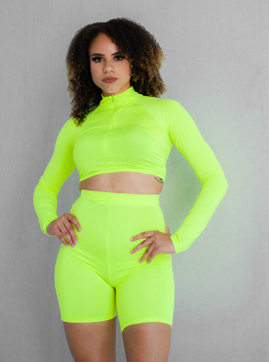 woman in neon green outfit, standing confidently