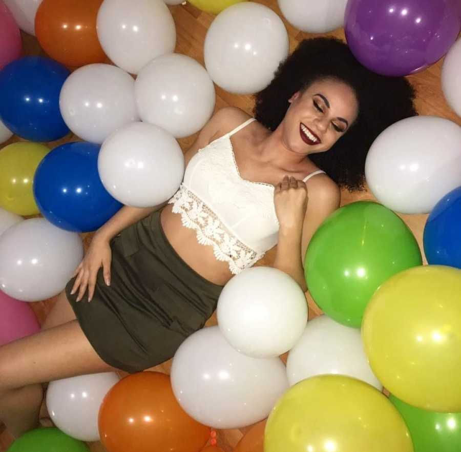 woman laying down with balloons