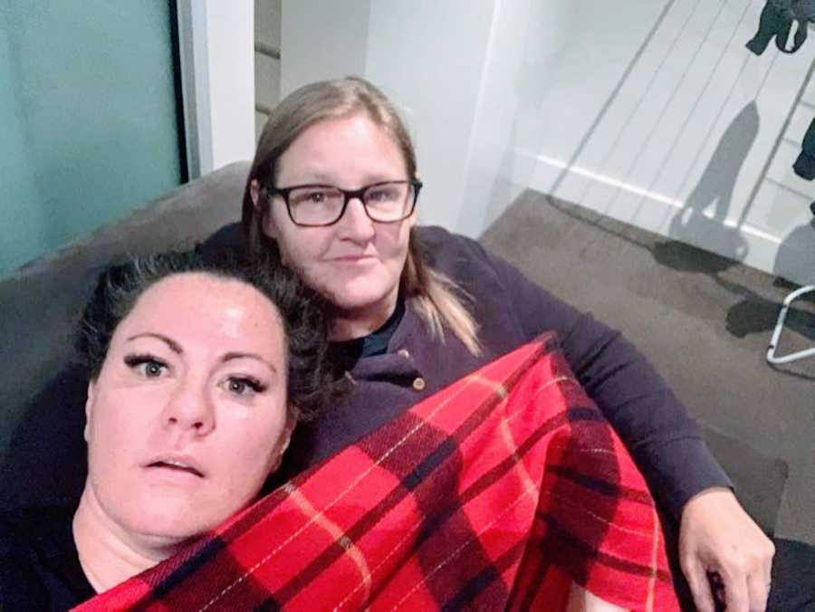 Couple cuddle on the couch under a red and black plaid fuzzy blanket