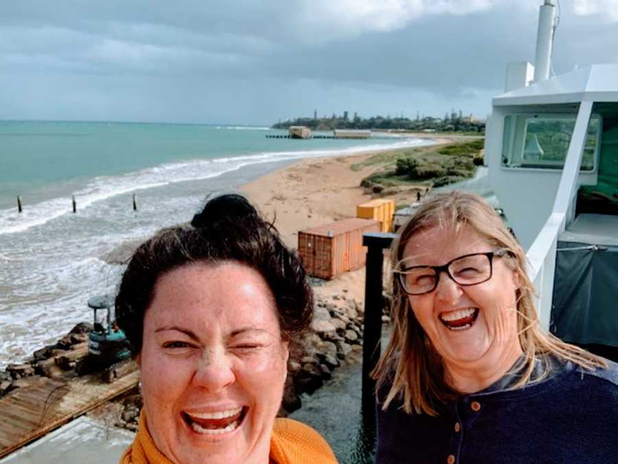 Lesbian couple take a silly selfie together while sight-seeing at the beach