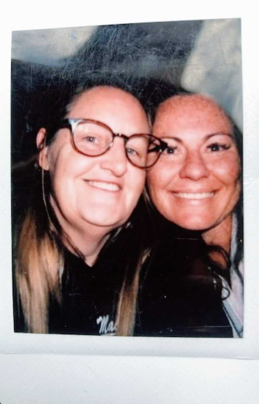 Lesbian couple take a polaroid photo together while on a date