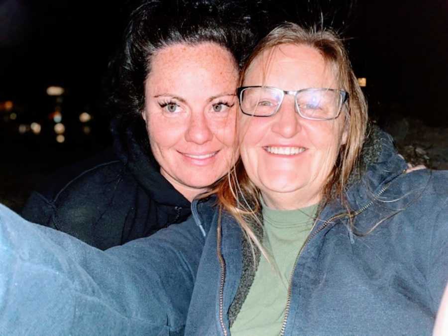 Lesbian couple take a selfie in the dark with the city lights behind them