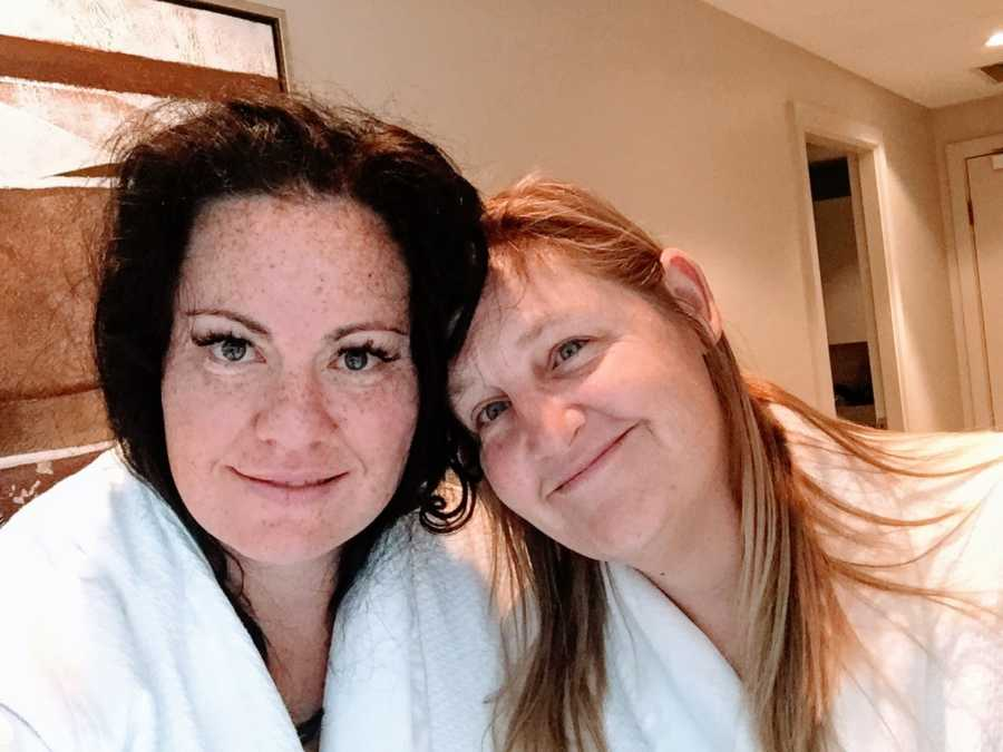 Lesbian couple in matching white, fluffy robes take a selfie while enjoying a romantic evening in a hotel