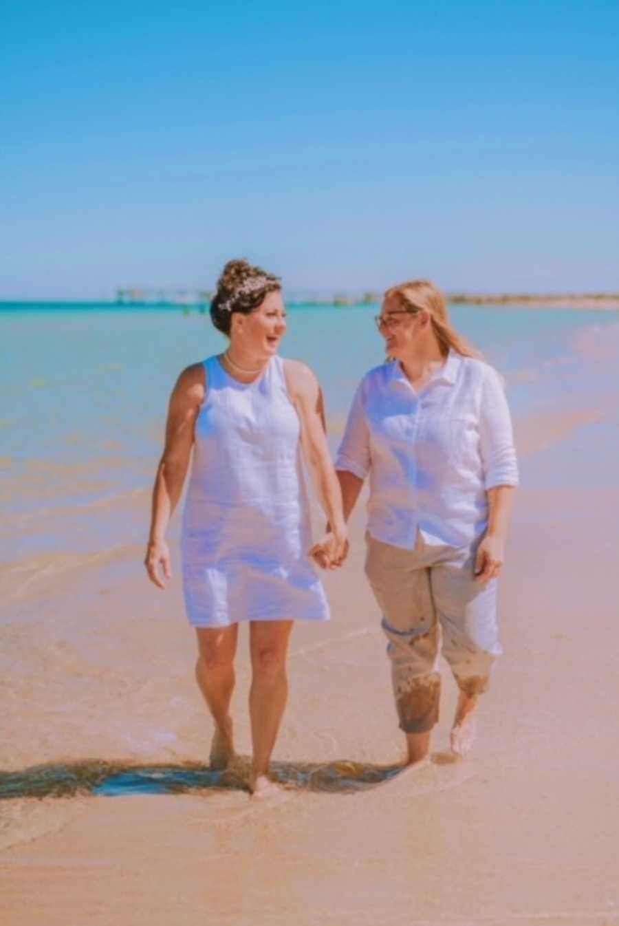Couple walk hand-in-hand down the beach after their wedding, celebrating their love