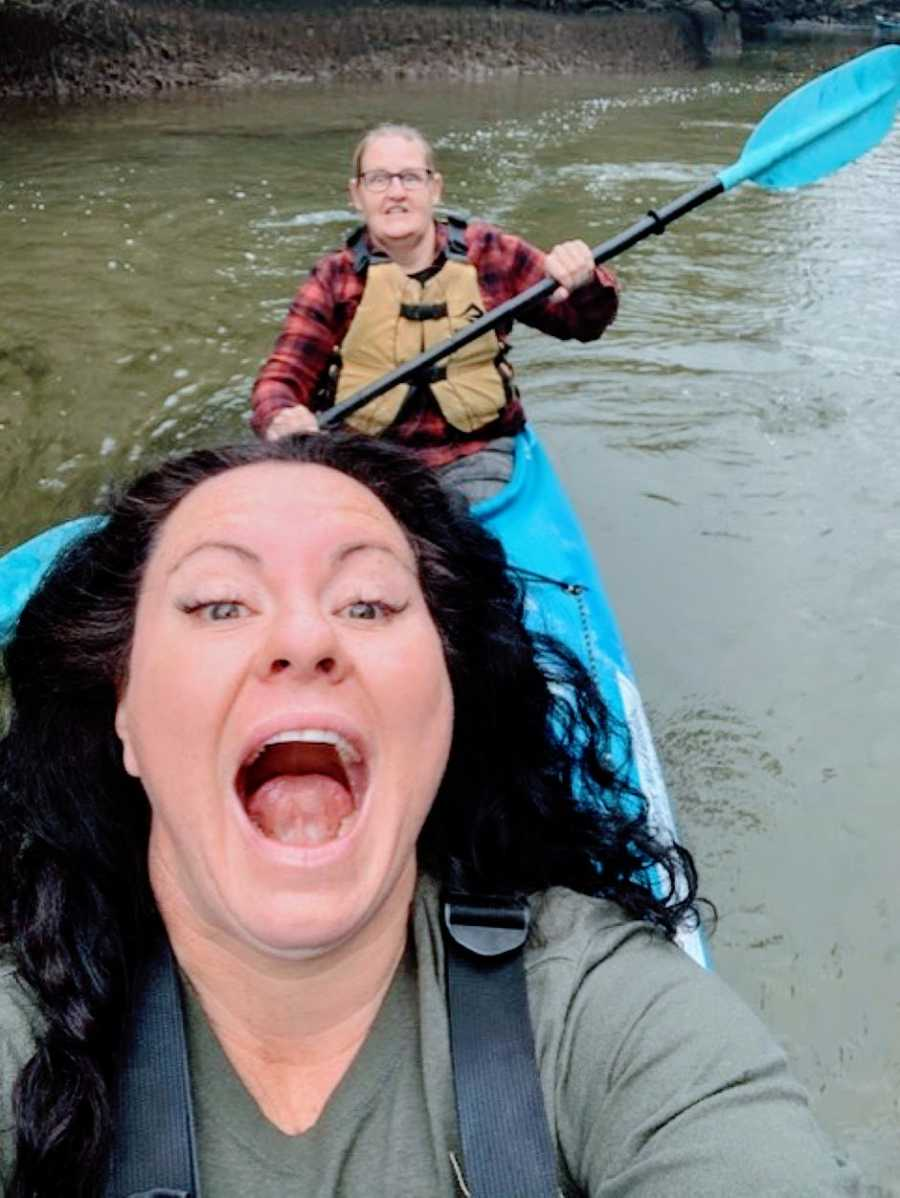 Couple take a silly selfie while out kayaking together on a river