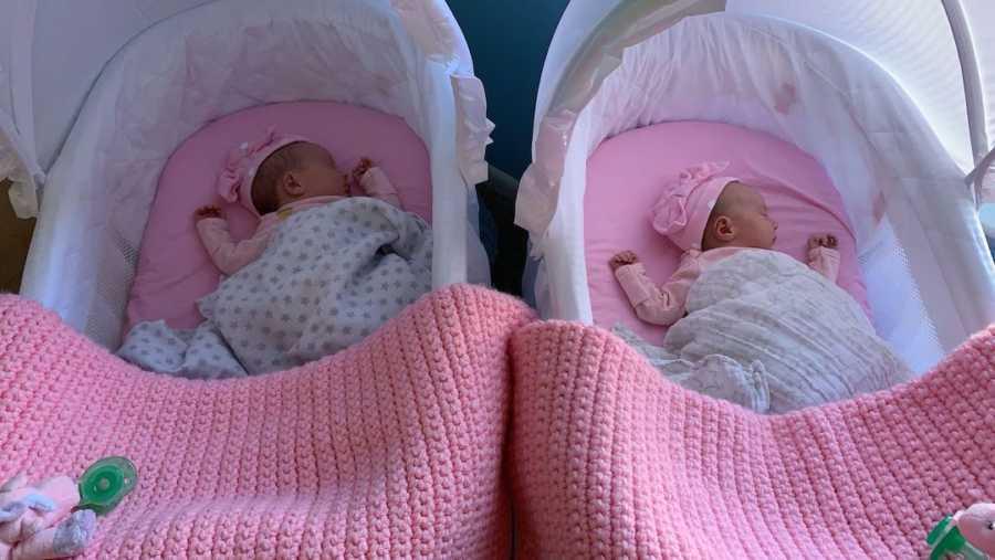 twin newborns in matching pink baskets