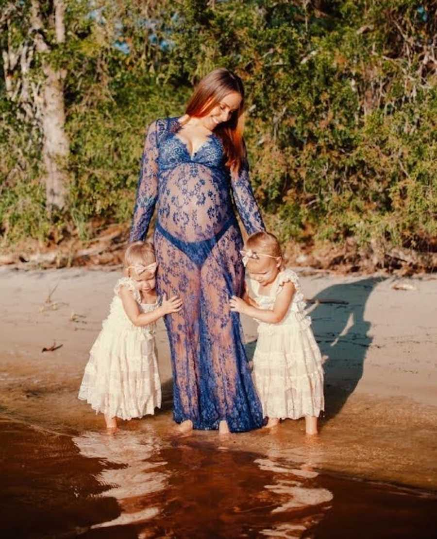 woman in lake with young twin daughters