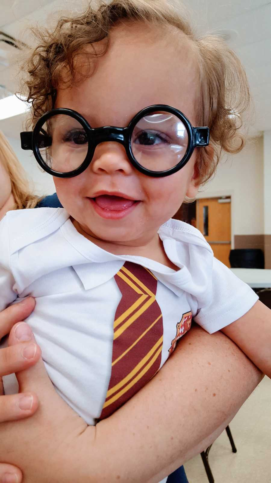 Little boy born during Harry Potter weekend smiles in Harry Potter onesie and glasses
