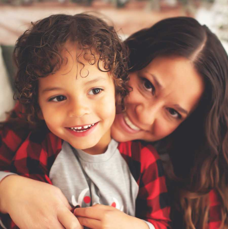 Woman hugs her adoptive son for a family photo while they both smile