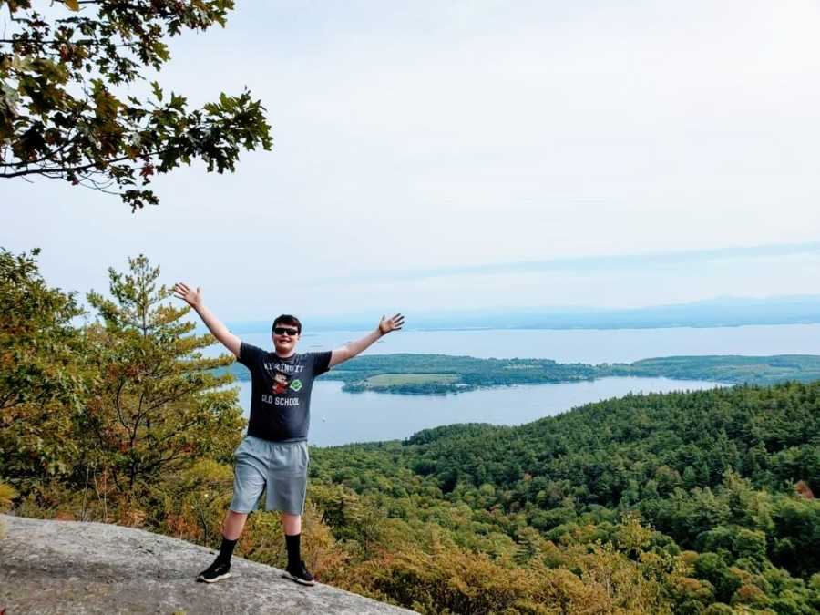 Photo of young boy celebrating the marvelous waterfront view during a hike