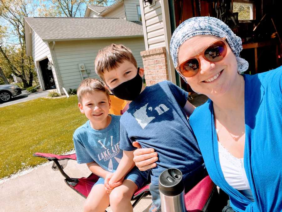 Boy mom takes a selfie with her two sons while they all enjoy some sun in their driveway
