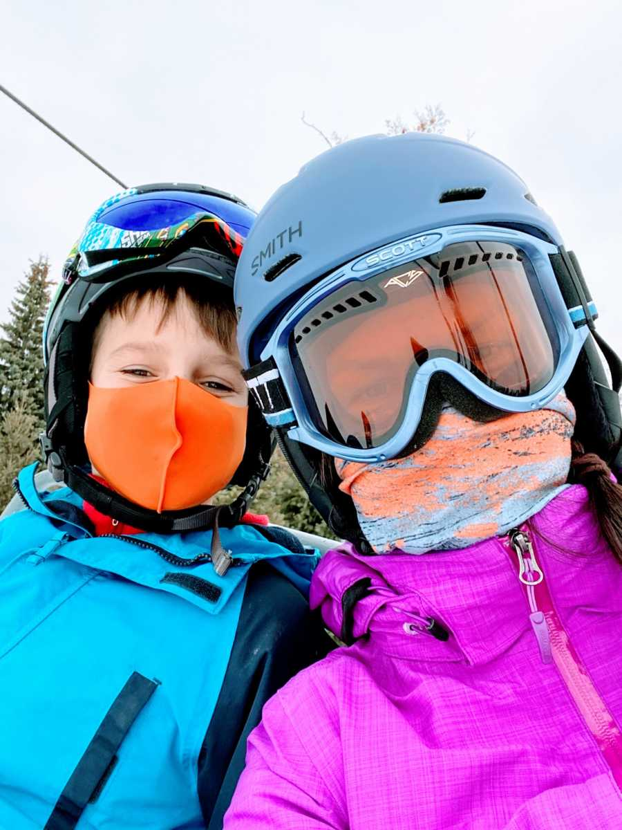 Mom takes selfie with her son, both in winter gear ready to go skiing