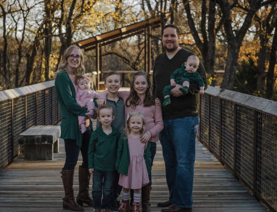 family of 8 outside on a bridge