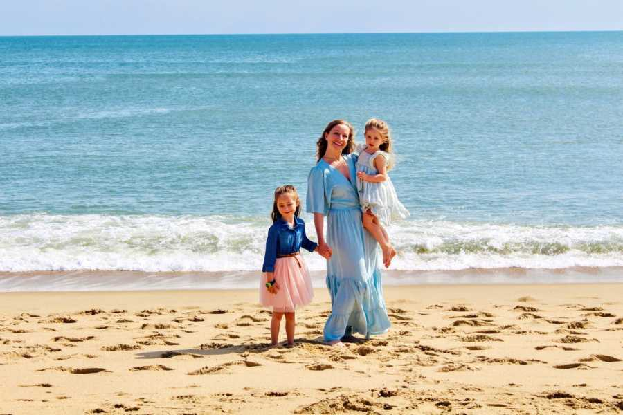 Girl mom takes a beautiful beach photo with her two daughters, all wearing flowy dresses blowing in the wind