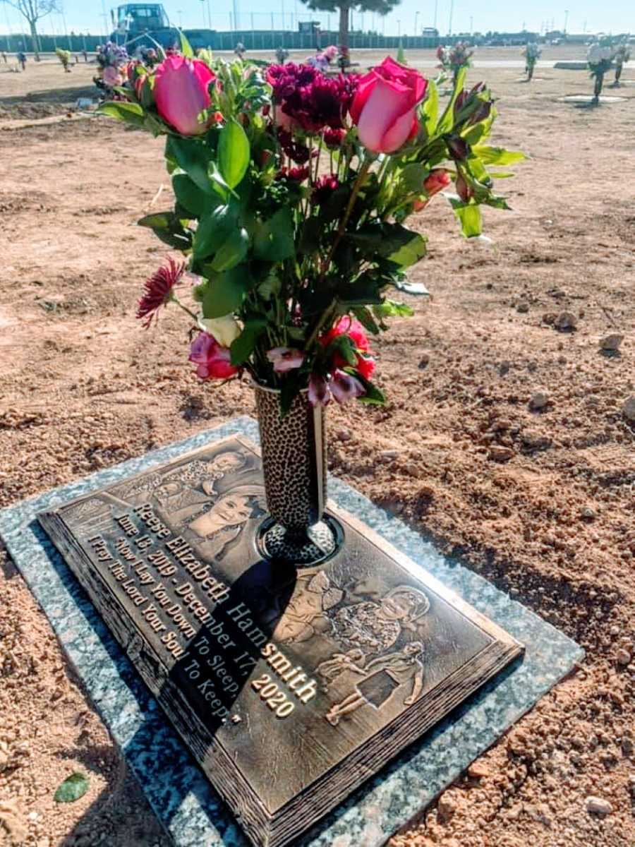 Photo of a child's grave with pink flowers on it