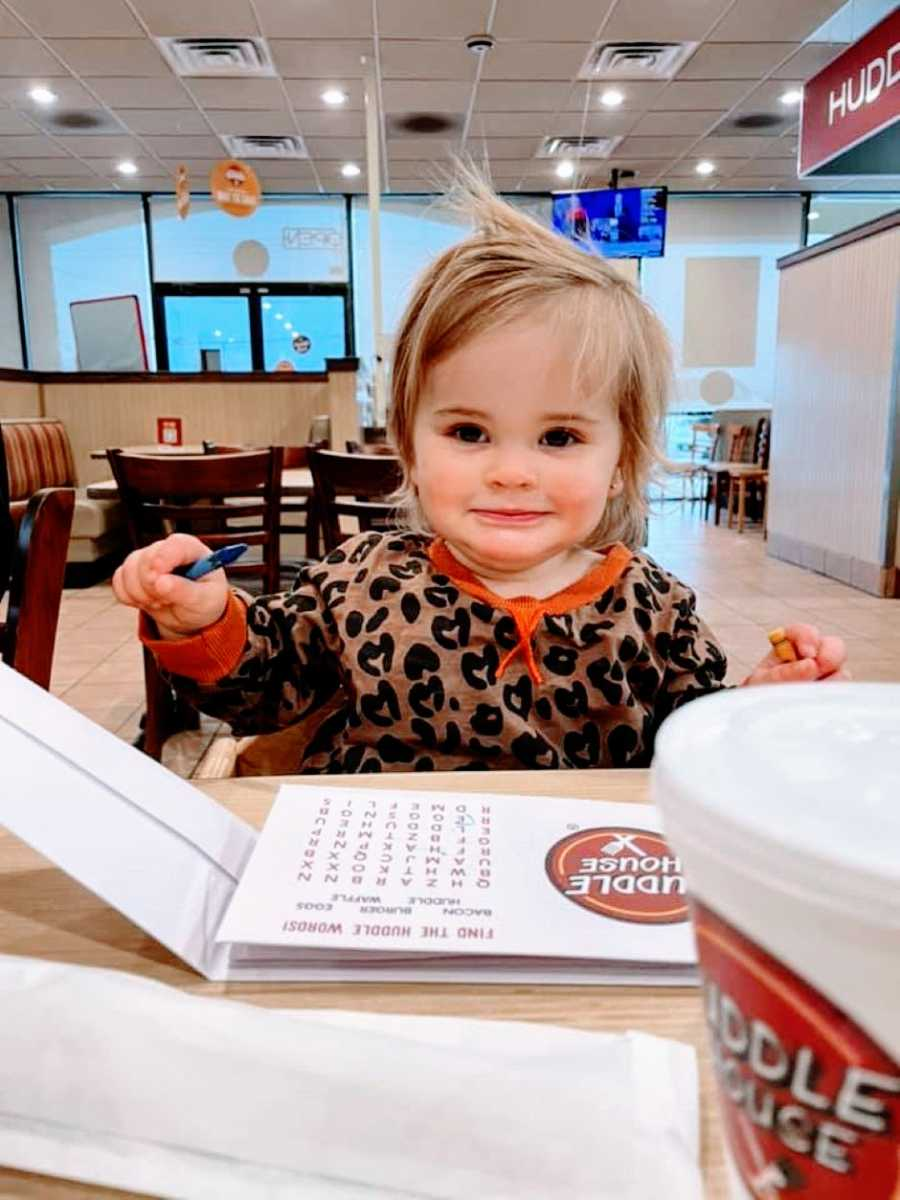 Little girl with heart-patterned shirt sits down at the Huddle House and colors