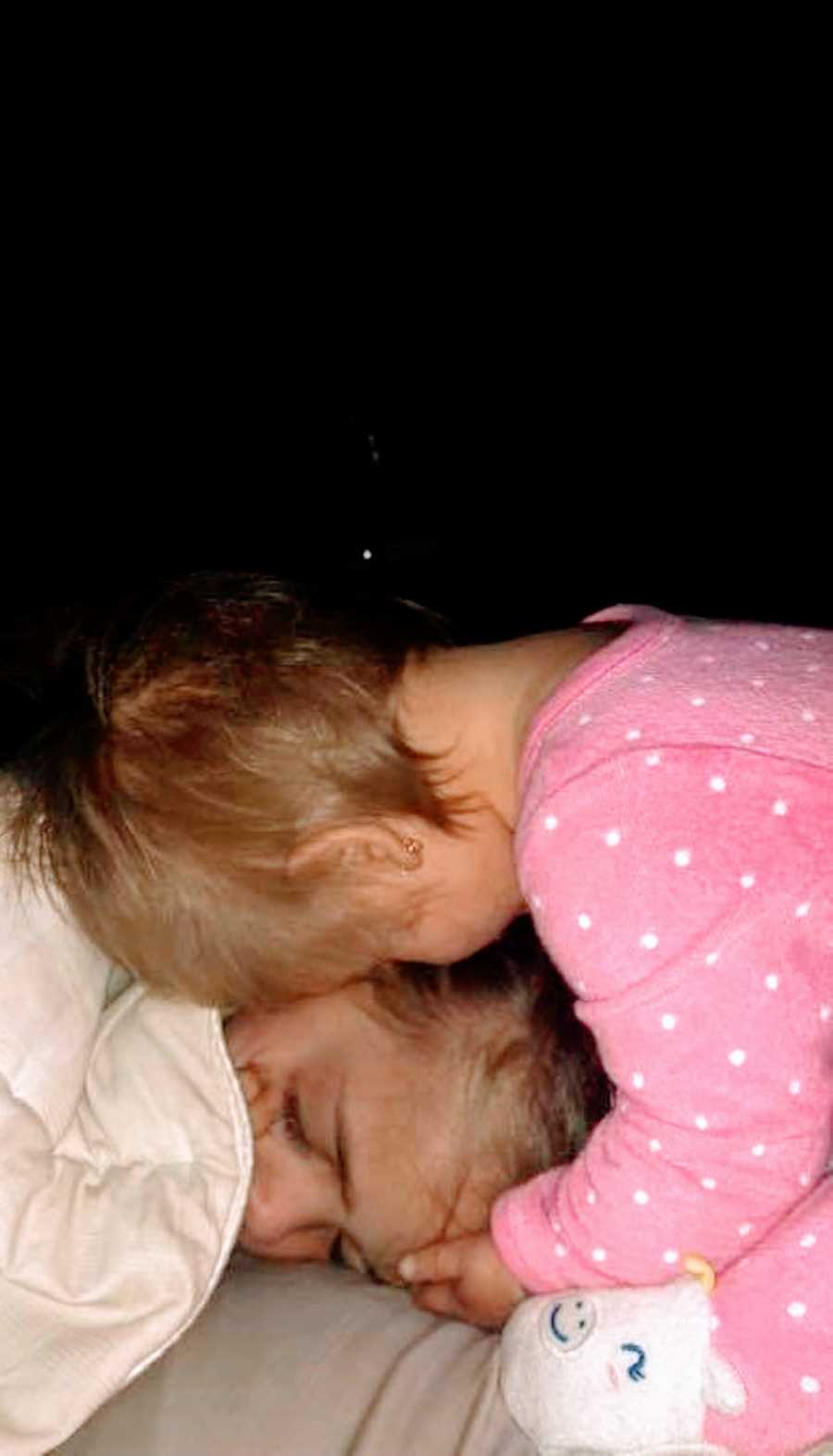 Two sisters cuddle in the dark at bedtime