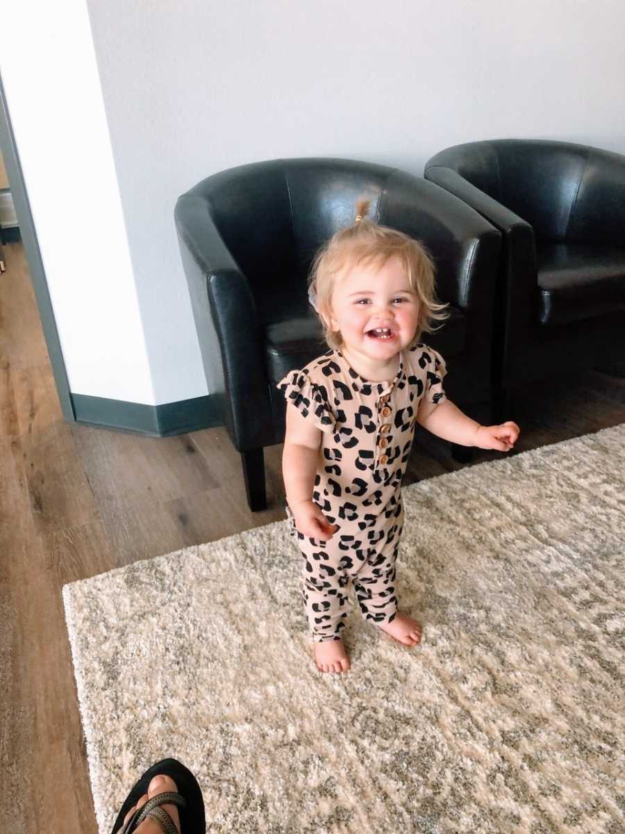 Little girl in patterned romper smiles while walking around the living room