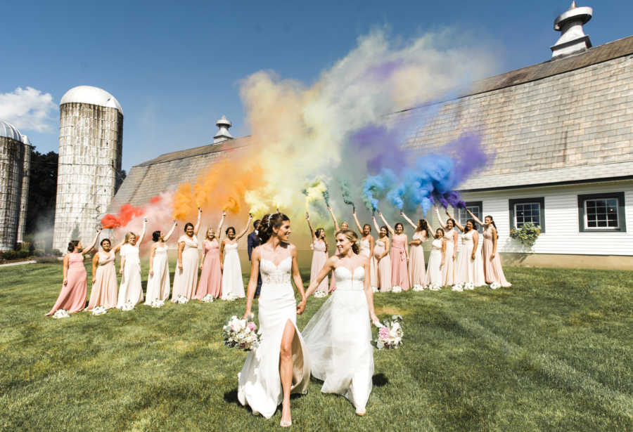 lesbian wedding photo on a hill. bridesmaids in pink and white dresses, rainbow smoke in the air