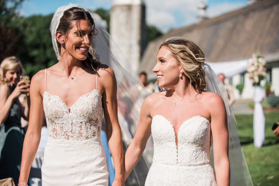 wedding photo of two brides holding hands and looking at each other