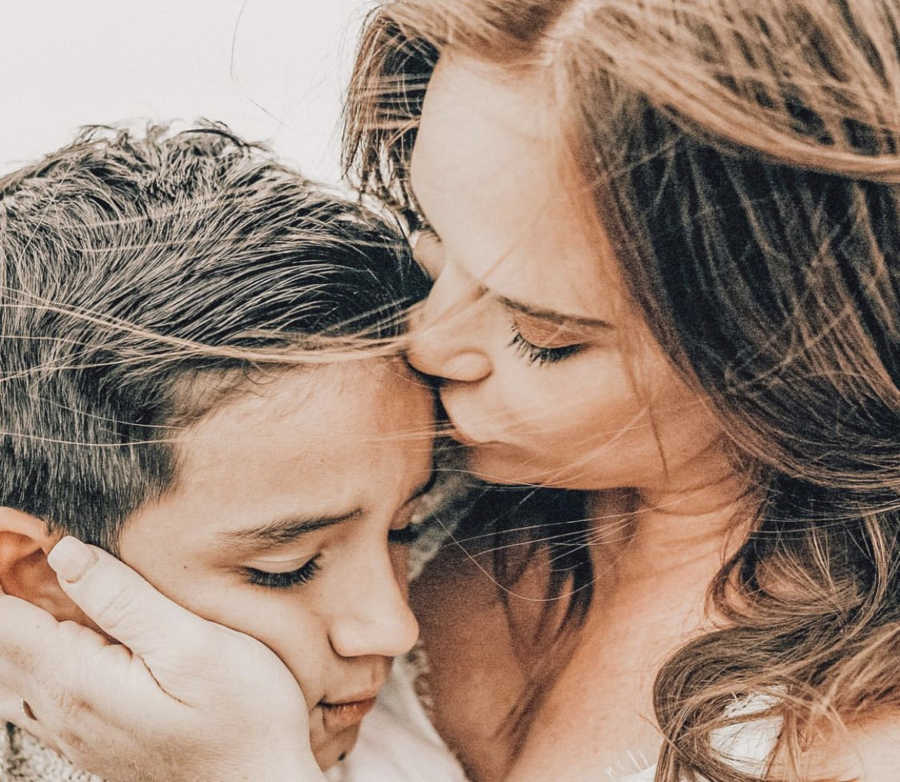 A mom kissing her son