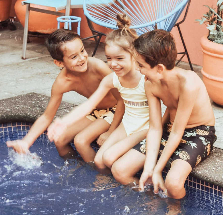 three kids playing in the pool