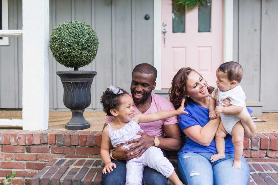 Family of four sitting on front steps of house laughing and smiling