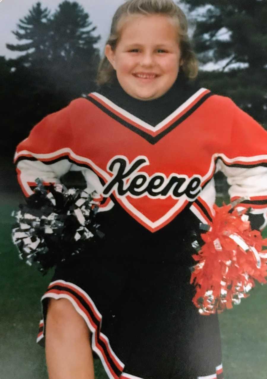 Young girl wearing cheerleading uniform smiling