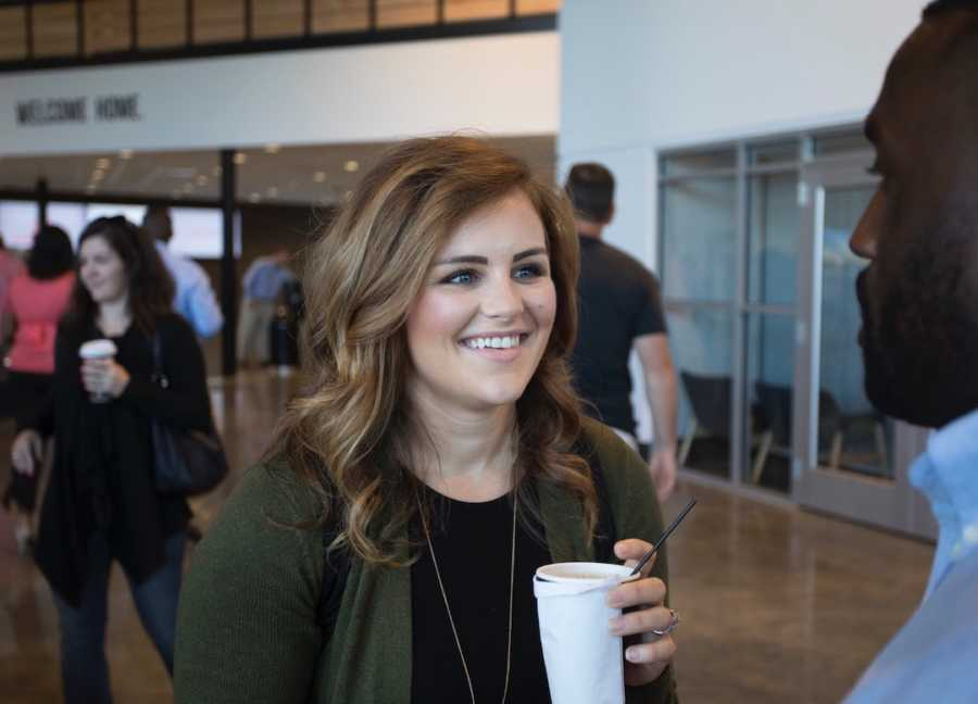 Woman at conference holding coffee cup and talking to man