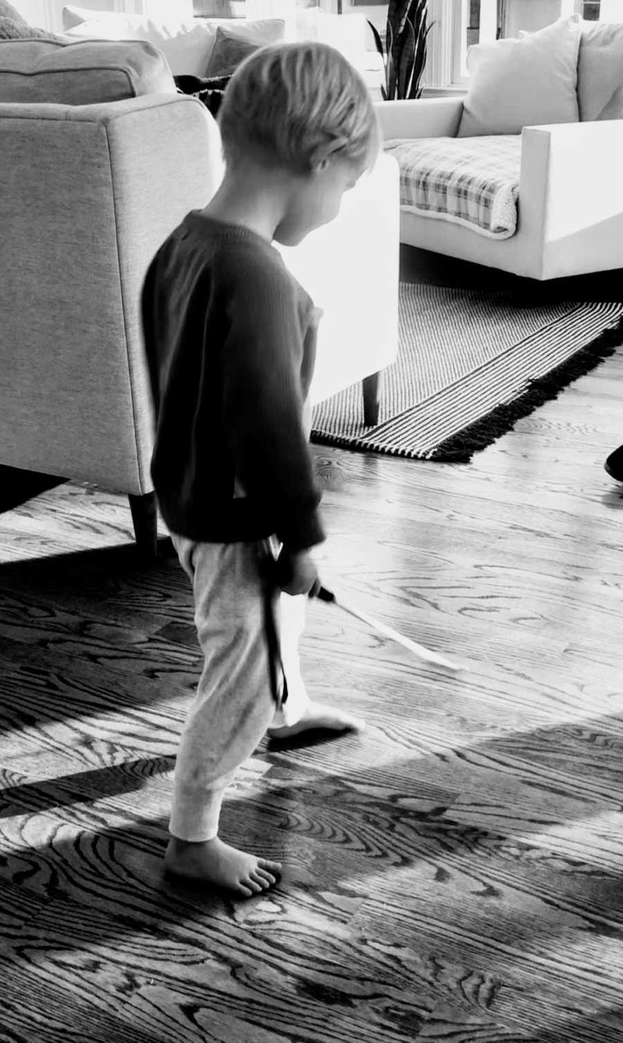 Black and white photo of young boy using walking stick