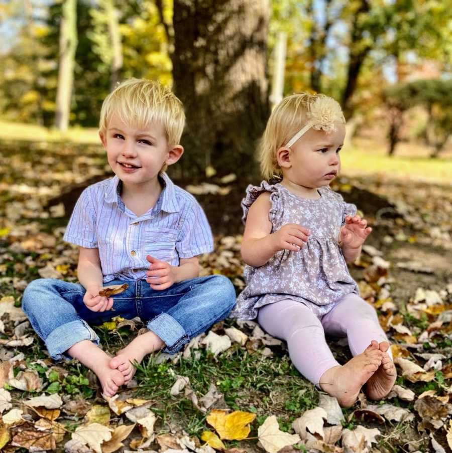 Brother and sister sitting outside on fall day