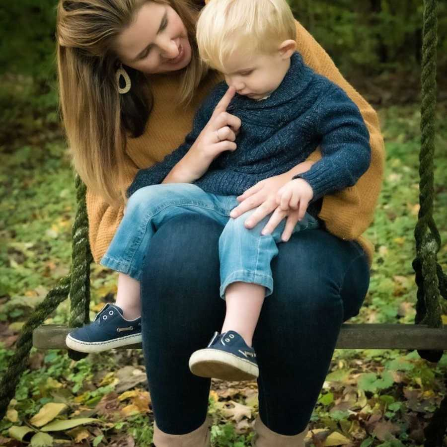 Mom sitting with son outside on lap touching his nose