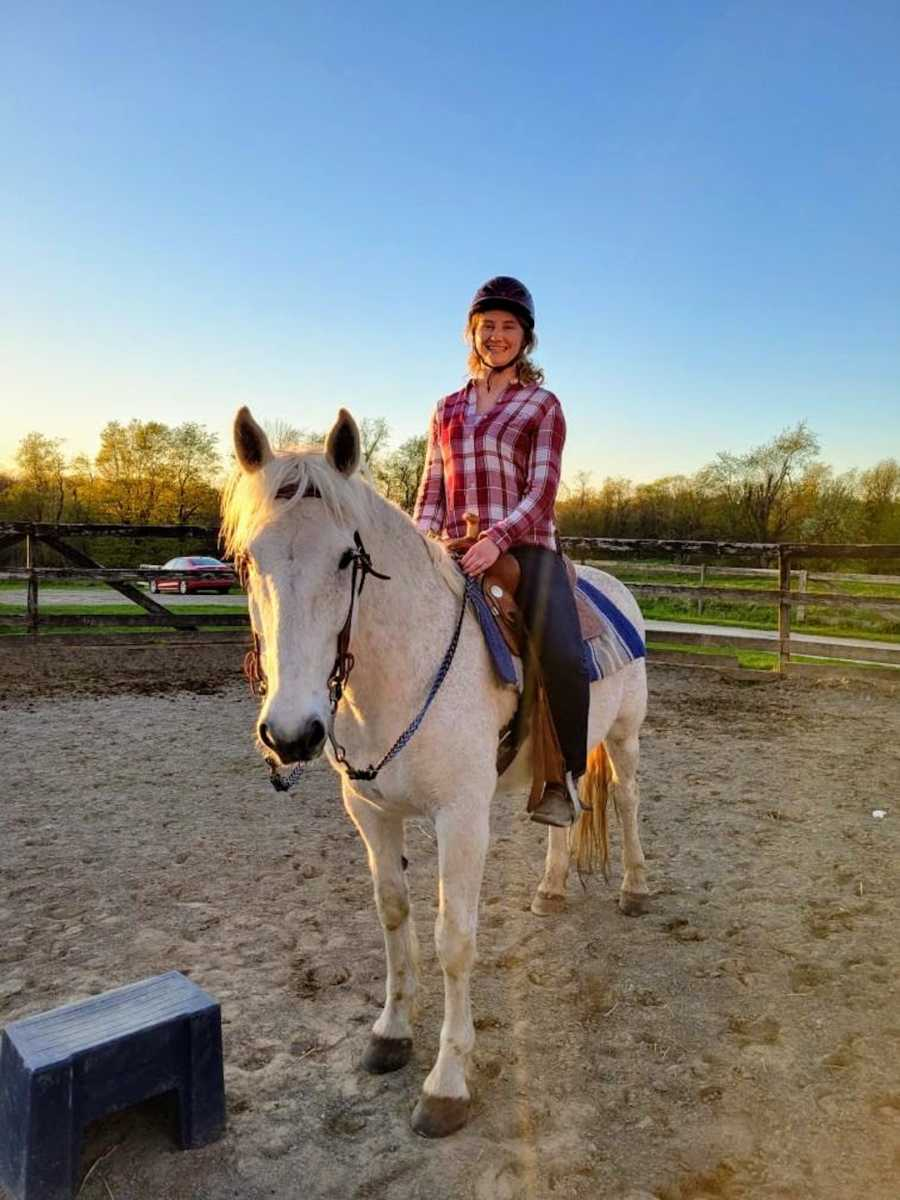 Woman riding a white horse with sunset in the background