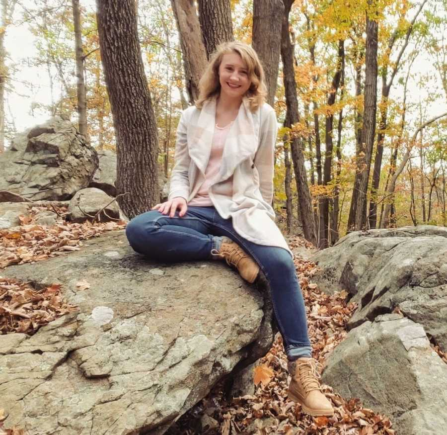 Woman sitting posed on a rock in the woods