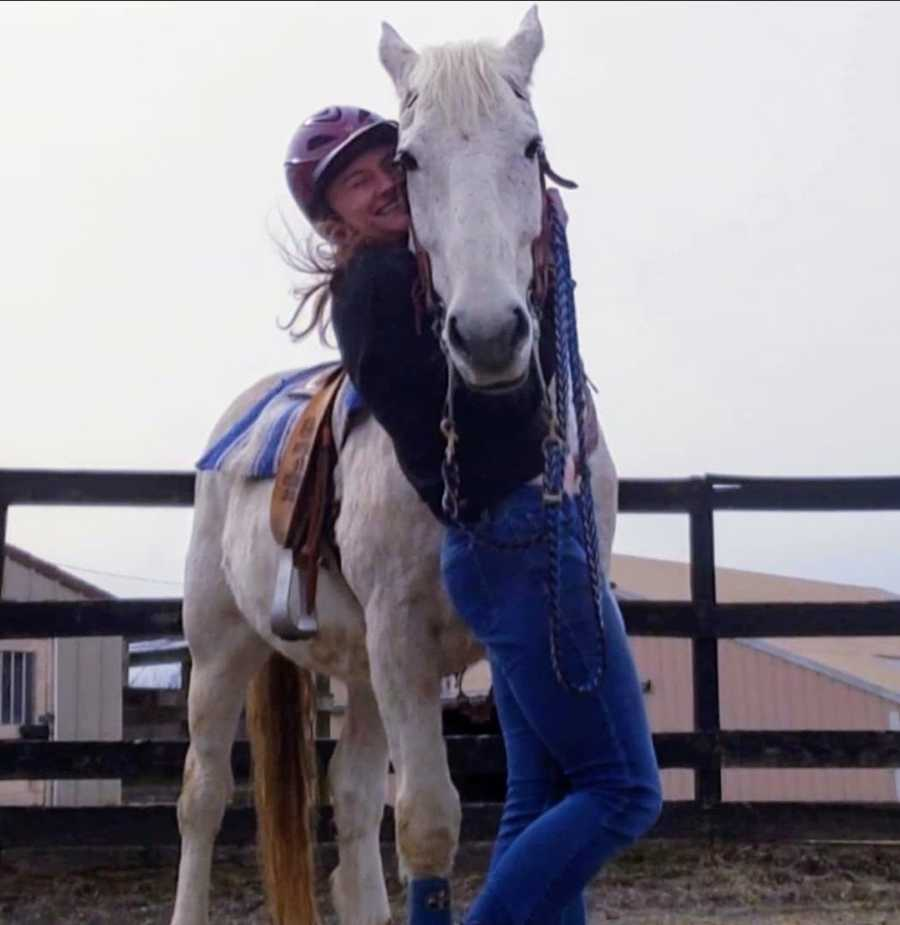 Woman wearing riding helmet hugging white horse