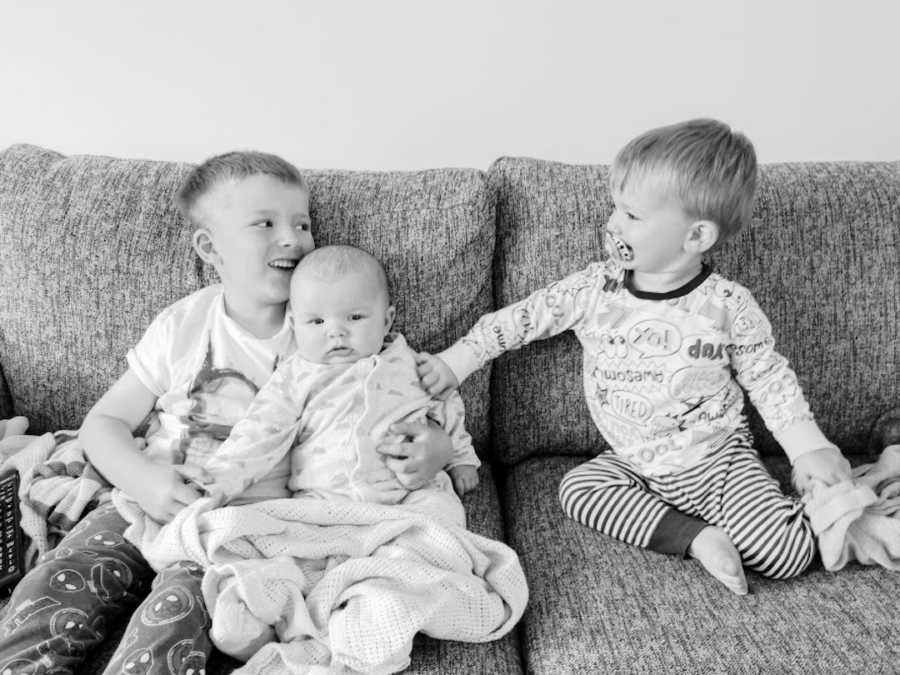 Three brothers sitting on couch black and white photo
