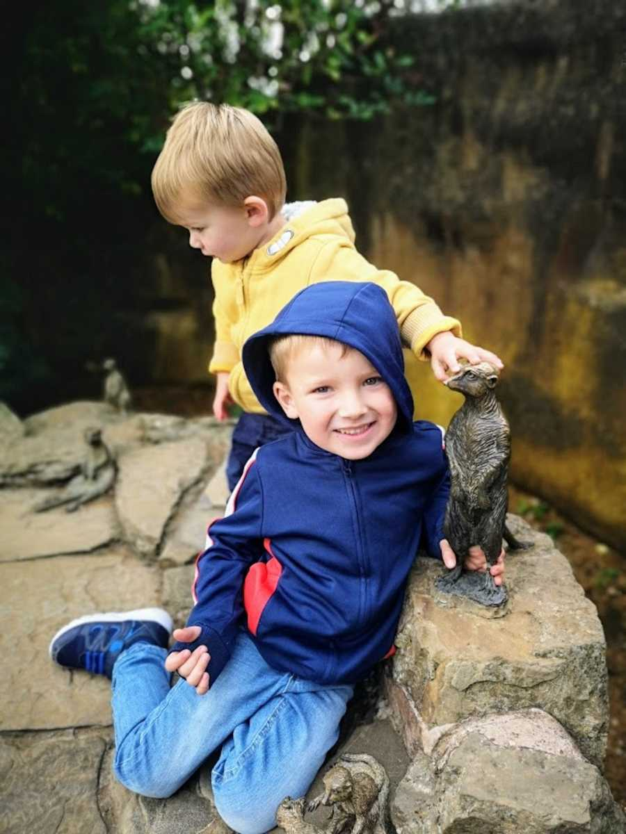 Two brothers playing on rocks wearing raincoats