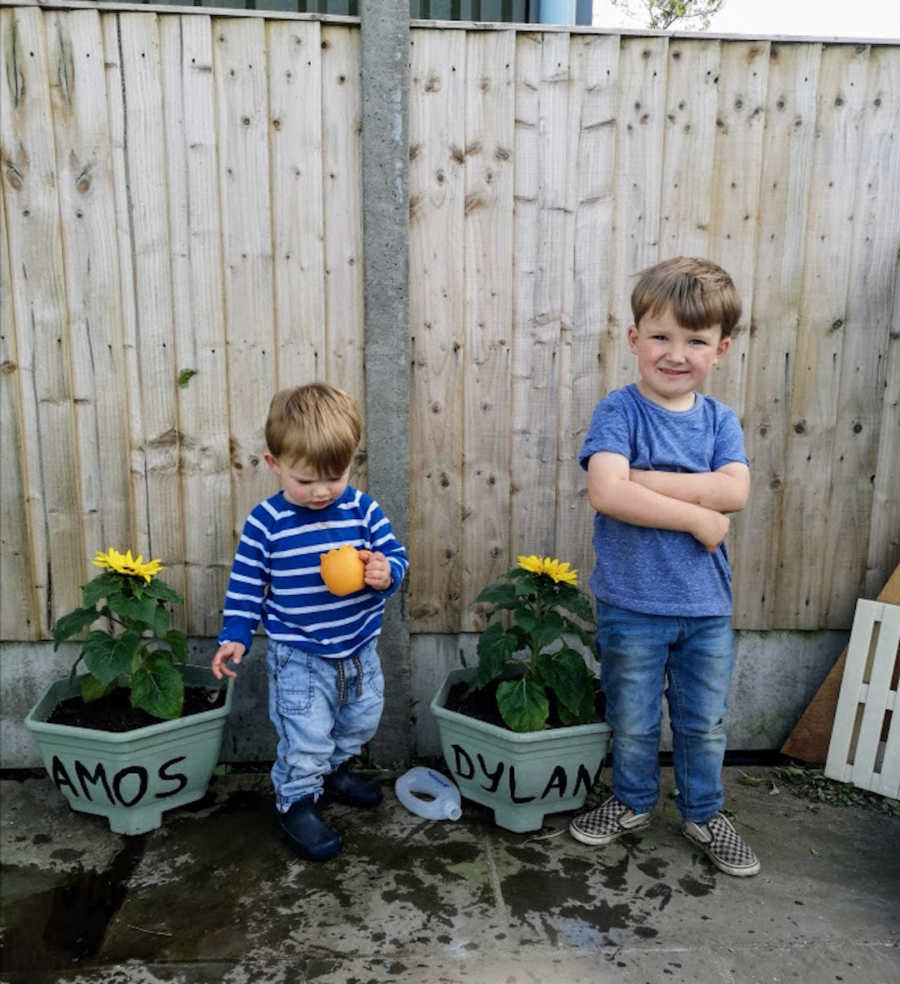 Two brothers wearing blue standing outside by garden