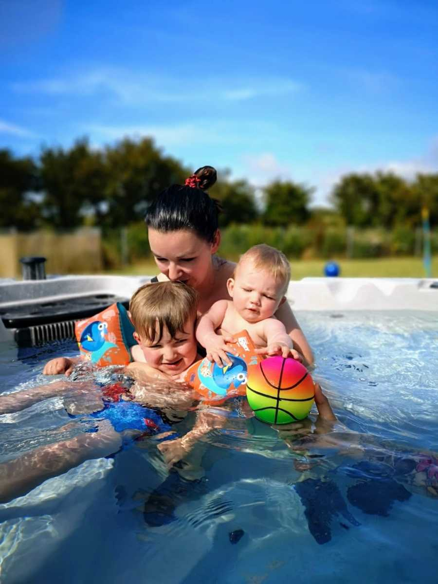 Mom with two sons swimming in pool outside