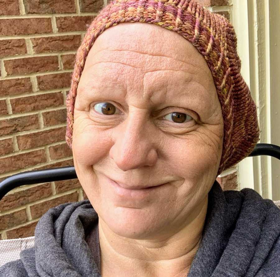 Bald woman wearing beanie taking smiling selfie in front of brick wall