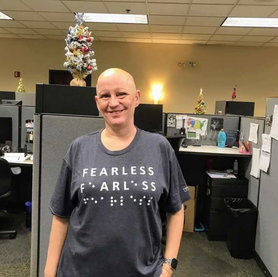 Bald woman standing in office smiling