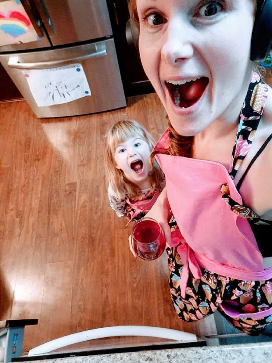 A neurodivergent woman and her daughter with mouths open in the kitchen