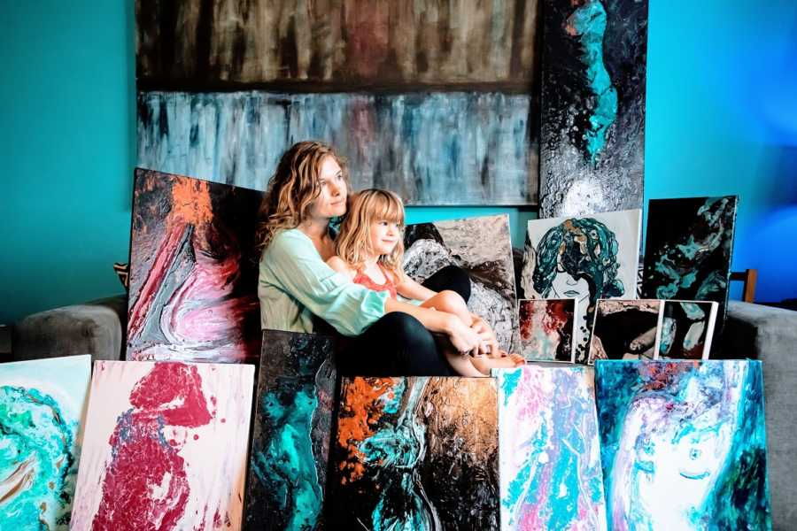 A neurodivergent woman and her daughter surrounded by artwork