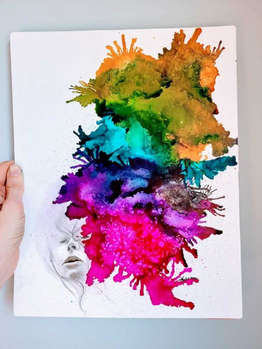 A piece of art with rainbow colors coming from a face