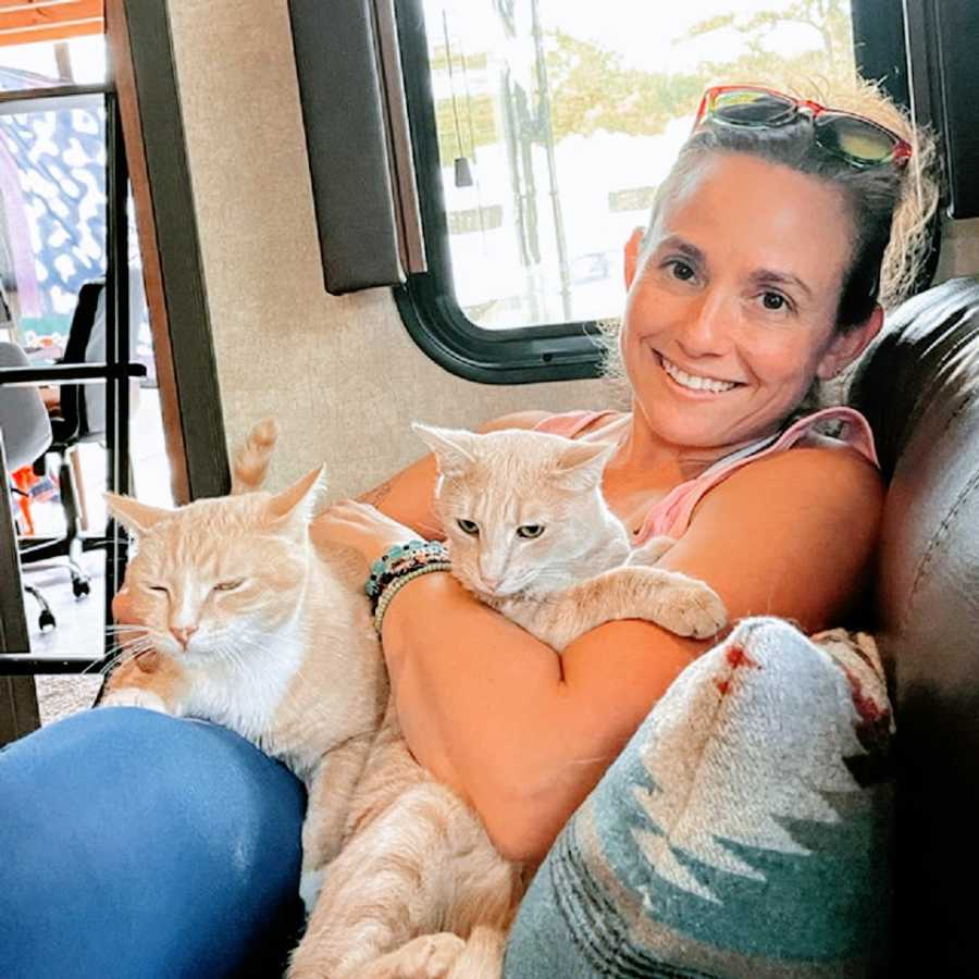 A woman sits with her cats inside her RV home