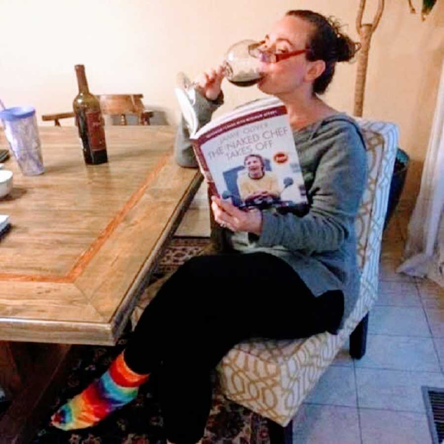 A woman reads a book while drinking a glass of wine
