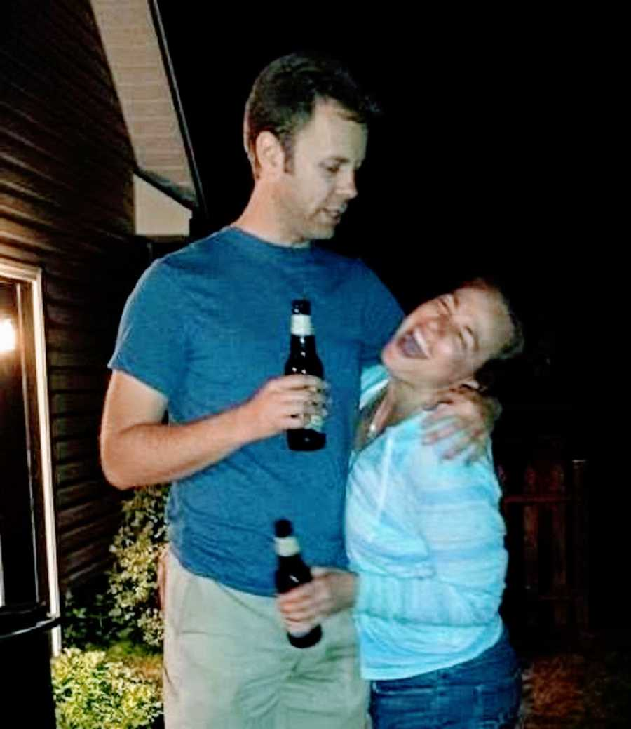 A woman and her husband stand outside holding beers